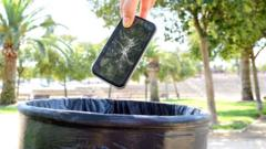 an-old-phone-going-in-the-bin