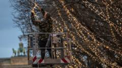 Workers hang lights on trees in Unter den Linden, a boulevard in the city centre in Berlin