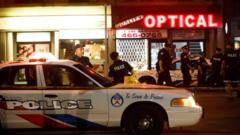 Toronto Police officers walk the scene at Danforth St. at the scene of a shooting in Toronto, Ontario, Canada on Sunday