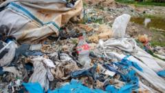 A Fanta plastic bottle is among the waste dumped and burned in Adana province in Turkey