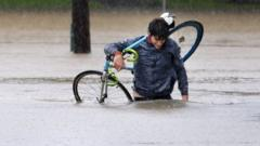 James Archiable carries his bike through the flooded intersection at Taylor and Usenet near downtown Houston, Texas, USA, 27 August 2017