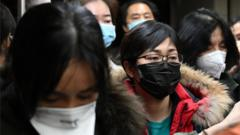Passengers from international flights wear protective face masks as they walk to the arrivals area at Beijing airport