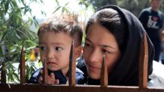 A woman and child look over a barrier at Moria camp