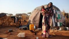 A Somalian refugee stands outside her home on the edge of the Ifo refugee camp