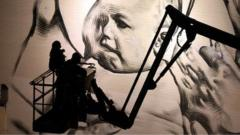 Two graffiti artists look at their painting of a baby in Bristol.