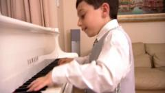 Eight year old boy playing piano