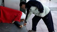 man gives coin to homeless person under a blanket