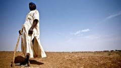 West African farmer stands on dry field