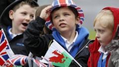 """A school boy watches Britain""""s Queen Elizabeth arrive by helicopter in Aberfan"""