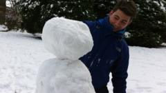 Ricky Boleto puts the head on his snowman.