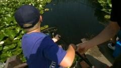 A young boy learns how to fish