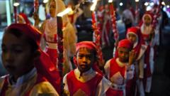 Children carry torches as Muslims parade on the streets ahead of Eid Al-Fitr