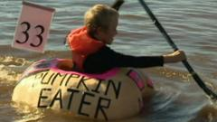 Child rowing inside a giant pumpkin on a lake