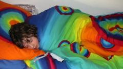 A boy sleeping in colourful bedsheets