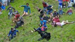 Competitors tumble down a hill