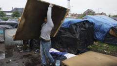 An Afghan migrant dismantles his makeshift shelter as he leaves a camp in Calais, northern France, 26 May 2014.