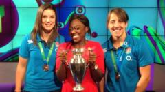 Katy Maclean, Ayshah and Sarah Hunter with Women's Rugby World Cup trophy