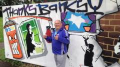 Denis Stinchcombe stands in front Thanks Banksy mural