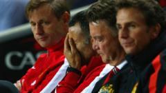 Ryan Giggs has his head in his hands, sat next to Louis van Gaal