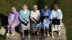 Five pensioners sat on park bench eating lunch