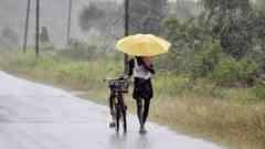 An Indian man holds an umbrella to protect himself from the heavy rains near Gopalpur