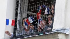 Children wave French flags from a school window