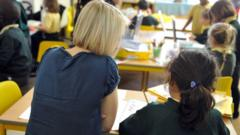A female teacher helps a young girl at Tolworth Infant School, a primary school for boys and girls aged 3 to 7.