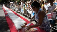 A woman serving up the massive cake in Rio.
