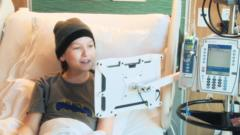 A boy using a computer touch screen in hospital
