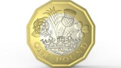 The new pound coin. It has twelve edges, with an outer golden ring and an inner silver ring. The design on the front shows a leek, thistle, shamrock and rose coming out of a crown.