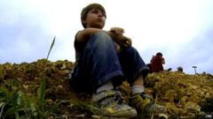 5-year-old Wylie from Dallas sitting on a mound of earth at the site where he uncovered a dinosaur fossil