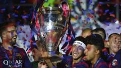 Barcelona's Neymar da Silva Santos Junior holds the trophy as Barcelona's players celebrate the win against Juventus in the UEFA Champions League Final