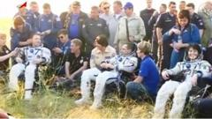 Astronauts Terry Virts, Anton Shkaplerov and Samantha Cristoforetti rest outside after landing
