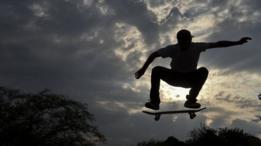Homem faz manobra de skate no ar