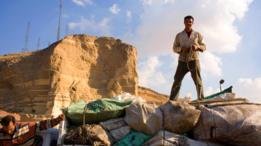 Homem amarra sacos de lixo em seu caminhão