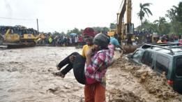 Homem carrega mulher nos braços em meio a lama deixada pelo furacão no Haiti