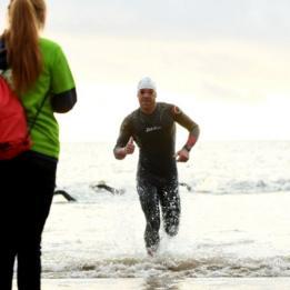 Homem sai do mar após horas de natação