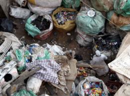 Mulher caminha por entre sacos de lixo
