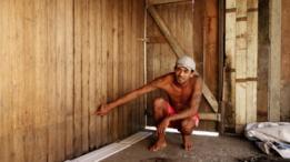 Um cidadão da área urbana do Envira mostrando a marca da água do enchente na sua casa
