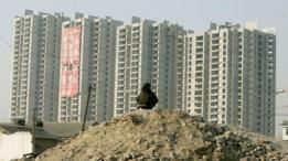 Homem na frente de um conjunto de prédios recém construídos