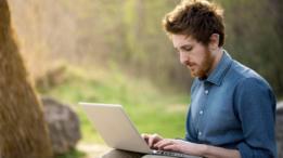 Em parque, homem trabalha sozinho com notebook