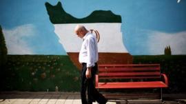 An Iranian man walks past a mural displaying the Iranian map