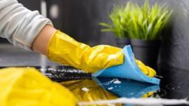 Pessoa limpando superfície de fogão elétrico com luvas