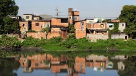 Casas precárias, sem pintura, na beira de canal poluído