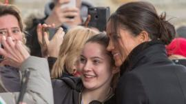 Meghan Markle poses for a photograph with a fan