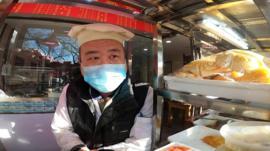 Beijing shopkeeper wearing a mask