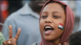 Female protester in Sudan with flag painted on her cheek