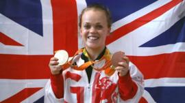 Ellie Simmonds holding her Paralympic medals