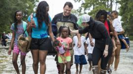 The Walker and Brown families walk out of the water at Memorial Drive and North Eldridge Parkway in the Energy Corridor of west Houston, Texas