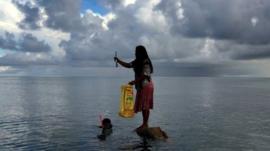 Woman stands on rock in the sea off Kiribati island